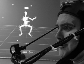 Laneth wearing motion capture outfit in front of wire-model on screen in background
